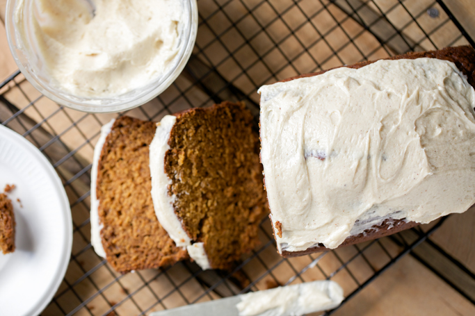 einkorn pumpkin bread sliced with cream cheese frosting
